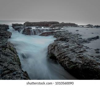 Misty dark tone Pacific Ocean and rocks near Newport Beach California