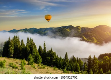Misty dawn in the mountains in summer. Hot air balloon.