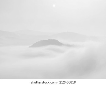 Misty dreamy landscape. Deep misty valley in autumn park full of heavy clouds of dense fog. Sandstone peaks increased from foggy background. Black and white picture.