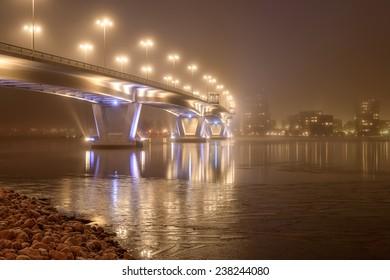 Misty evening scenery with illuminated bridge and ice