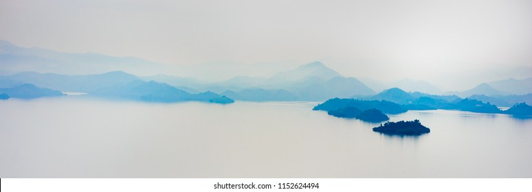 Misty foggy landscape with lake and mountains , early morning, calm and quiet, pastel color, Kivu, Rwanda, soft focuse