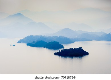 Misty foggy landscape with  lake and mountains , early morning, calm and quiet, pastel color, Kivu, Rwanda