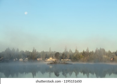 Misty foggy morning on the island lake with a full moon in the clear blue sky. Pacific Northwest, Washington state.