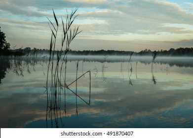 Misty lake in a cold early autumn morning. Morning nature scene (landscape): sky, clouds and fog (mist) and lonely boat reflected on the water surface. Can be used as a background or wallpaper.