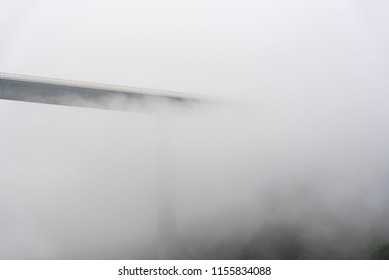 Misty landscape with the tallest viaduct in Germany, the Kochertalbrucke, crossing over wooded hills, overrun by fog and clouds, near Braunsbach town