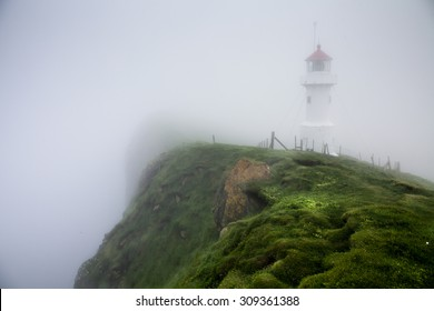 Misty lighthouse. Lighthouse on Mykines island, Faroe Islands, Denmark
