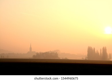 Misty morning in the country, church, trees, sunrise.