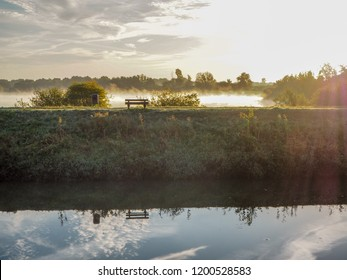 Misty morning landscape at the Dijle river and Mechelen Marsh nature park with an idyllic bench in Muizen, Belgium