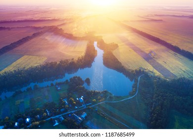 Misty morning, rural landscape. Aerial view from above at village, lake, river and arable fields