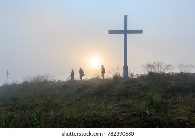 Misty morning sunrise dew on wild mountain grassy hill with religious crosses and family walking by pass on sunshine background.