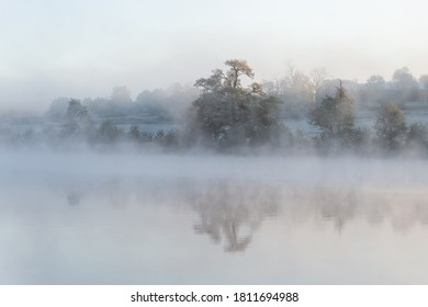 Misty morning at sunrise, the fog swirls around the autumn landscape. The mist, sunshine and trees create a dreamy scene. Background with place for text, copy space.