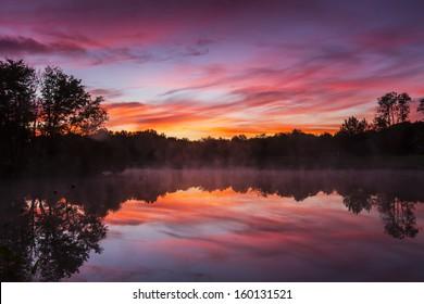 Misty morning sunrise reflection in a lake