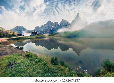 Misty morning view of Baita Segantini mountain refuge with Cimon della Pala peak. Exciting summer scene of Dolomiti Alps, Rolle pass, Trentino, Italy, Europe. Beauty of nature concept background.