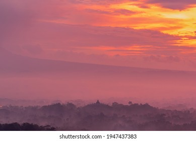 Misty Morning view of Borobudur with layers of trees seen from Setumbu with burning sky