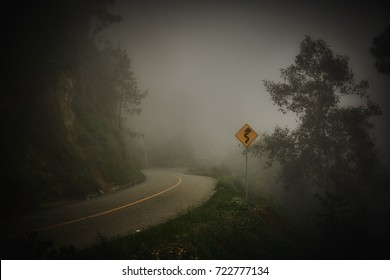 Misty mountain road with yellow sign danger