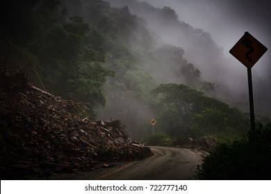 Misty mountain road with yellow sign danger and rocks fallen
