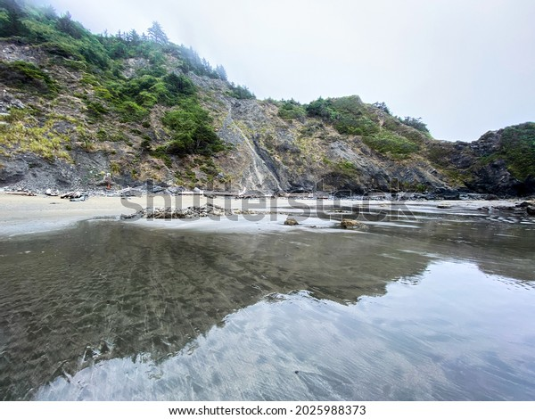 a misty mountain rock formations along ocean seaside shore with bright reflections in still low tide water