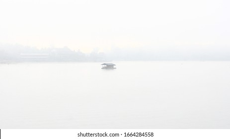 misty river. raft house covered in fog from water moisture. cool morning scene in tropical country lake. still water pool in a jungle like forest. serenade peaceful rural wilderness.