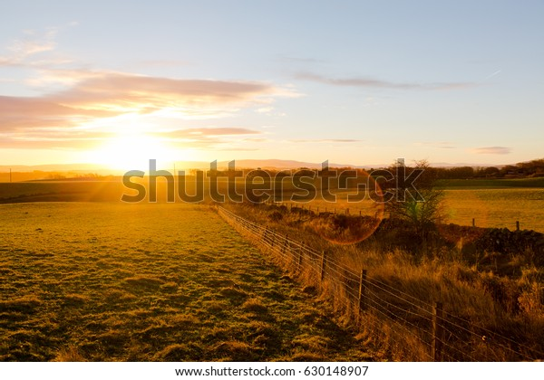 Misty rural landscape in sunrise light, Scottish Highlands, United Kingdom. Golden hour light, contrasting shadows to green grass and orange sun.