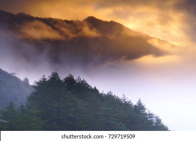 Misty scenery in Taroko National Park,With pinaster on hillside stack by layer and sunrays shining through Fiery clouds in the background.