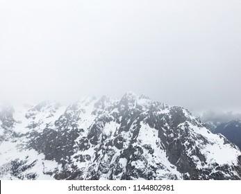 Misty snow covered alpine peaks