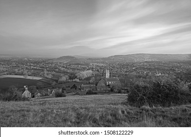 A misty start to the day over the Stroud valley looking towards the Vale of Berkeley in the foreground is All Saints Church, Selsely, The Cotswolds, Gloucestershire, UK