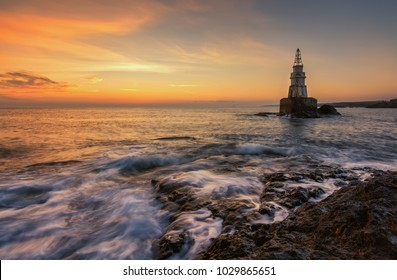 Misty sunrise of the lighthouse in Ahtopol, Bulgaria. Blue hour seascape. Long exposure