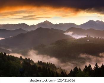 Misty sunrise in the mountains of Kamnik Savinja Alps and rolling fog in Skofjelosko Hills with St Thomas church near Ljubljana Slovenia
