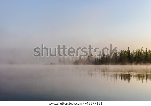 Misty sunrise over a lake and forest
