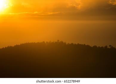 Misty sunrise view on crater ridge