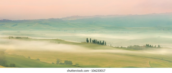Misty Tuscan hills one early morning in San Quirico d'Orcia with view on Belvedere villa