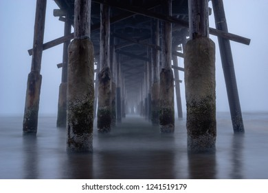 Misty water surrounding the bottom of a pier on an overcast day. Cold and desolate.