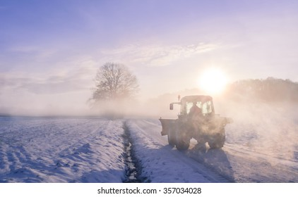 Misty Winter landscape with a countryroad, warmed up by sunrise and  wrapped in a coat of fog. From the mist it can be seen a silhouette of a farmer driving its tractor on a frosted field.