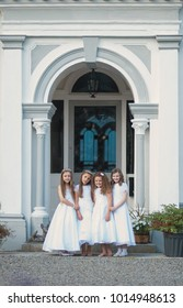 MITCHELSTOWN, IRELAND - May, 27, 2013: Four little girls in a white dresses on her First Holy Communion day in front of Ballinwillin  House