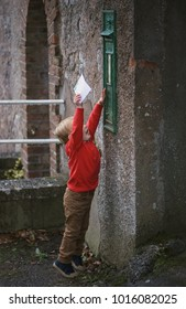 MITCHELSTOWN, IRELAND - November, 26, 2017: Little boy with letter to Santa on a front of vintage irish post box