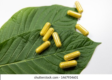 Mitragyna speciosa or kratom leaves with medicinal products on wooden table.