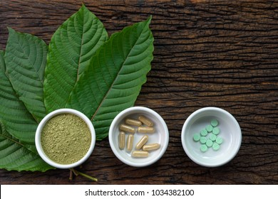 Mitragyna speciosa (kratom) leaves with medicine products in powder, capsules and tablet in white ceramic bowl with wooden texture on background
