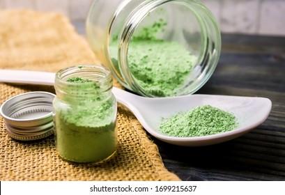 Mitragyna speciosaor Kratom powder in ceramic spoon and glass jars on table with hemp cloth