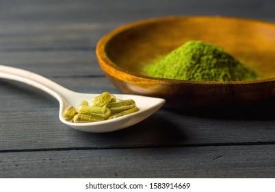 Mitragynina speciosa or Kratom powder in wooden bowl and Kratom capsules in ceramic spoon on table
