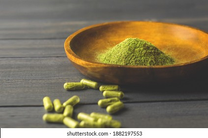 Mitragynina speciosa or Kratom powder in wooden bowl and Kratom capsules on table