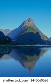 Mitre Peak reflected in the water of the Milford sound, New Zealand