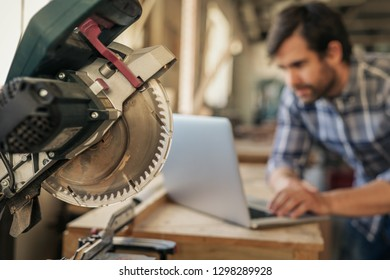 Mitre saw on a workbench with a focused young woodworker doing research on a laptop in the background