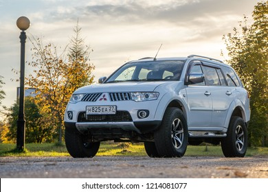 Mitsubishi Pajero Sport and trees in autumn on a sunny day. Khabarovsk, Russia. October 12. 2018