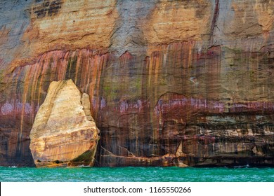 A mitten shaped rocks against the a stone cliff at Pictured Rocks National Lakeshore in Northern Michigan. These mineral laden cliffs have a painted look in the sandstone rock formations