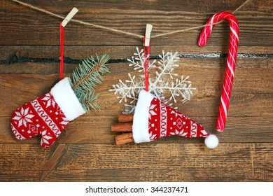 mittens with fir branches and Christmas candy weigh on the rope on wooden background