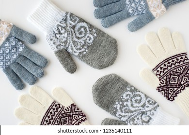 Mittens and gloves scattered on a white background. View from above. Warm clothing for cold seasons in the form of mittens and gloves. Clothes for hands on a white background.