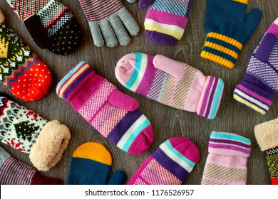Mittens for winter. View from above. Many multicolored mittens on a wooden background. Warm clothing for hands in the cold season.