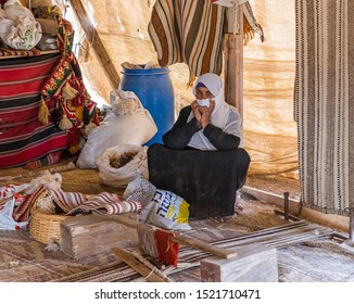Mitzpe Ramon, Israel, September 28, 2019 : Bedouin woman sits near a primitive loom in a Bedouin tent in a Bedouin village near the Mitzpe Ramon city