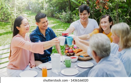 Mix aged big family enjoy having outdoor party eating food at backyard home, warm and happy lifestyle family concept