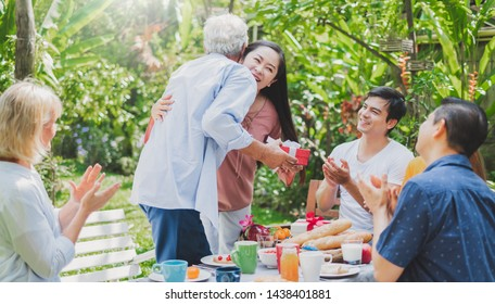 Mix aged big family enjoy having outdoor birthday party eating food at backyard home, warm and happy lifestyle family concept
